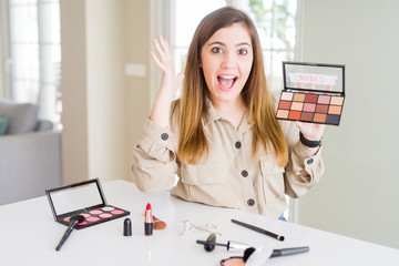 Beautiful young woman using make up cosmetics applying color from palete very happy and excited, winner expression celebrating victory screaming with big smile and raised hands