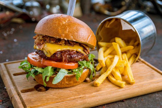 Hamurger with bacon and vegetables with french fries on dark rustic concrete table
