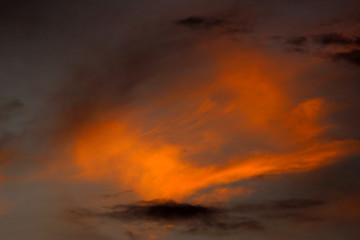 A cloud glows orange in a sunset sky