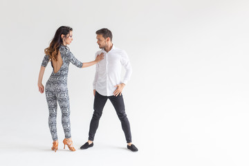 Social dance concept - Active happy adults dancing bachata together over white background with copy...