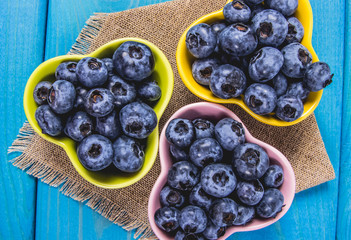Raw fresh huckleberry in a bowl. Wooden background.