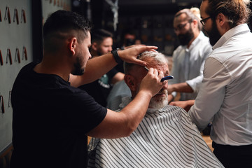 two professional masters working with old man, helping him to be handsome and stylish. close up photo