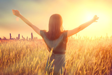 Happy autumn woman raising hands over sunset sky, enjoying life and nature. Beauty female on field looking on sun. Silhouette of girl in sunlight rays. Fresh air, environment concept. Dream of flying Fototapete