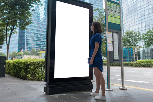 Woman standing near blank advertising lightbox on the bus stop, mock up