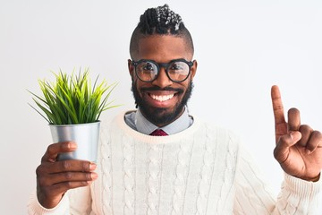 African american man with braids holding plant pot over isolated white background surprised with an idea or question pointing finger with happy face, number one