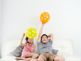 Asian sister and her brother playing balloons at home together, lifestyle concept.