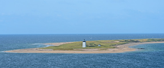 A lighthouse marks the end of a spit of land protruding out into the harbor at Provincetown, Massachusetts.