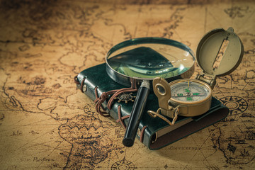 old map with compass, notebook and magnifying glass. The concept of searching for interesting places or treasures around the world.