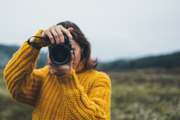Wall Mural - photographer girl take photo on camera on background autumn froggy mountain, tourist shooting nature mist landscape, hobby concept, copy space