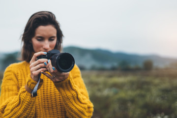 Wall Mural - photographer traveler take photo on video camera closeup on background autumn froggy mountain, tourist shooting nature mist landscape, hobby adventure concept, copy space mockup