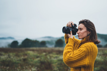 Wall Mural - photographer traveler take photo on video camera closeup on background autumn froggy mountain, tourist shooting nature mist landscape outdoor, hobby concept copy space mockup