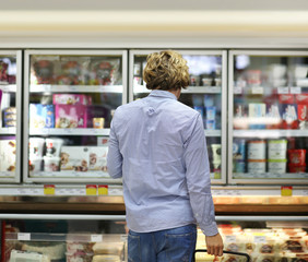 Man choosing frozen food from a supermarket freezer