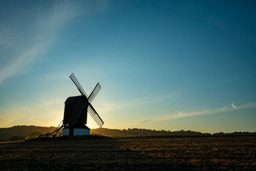 Windmill in a picture with sun rising behind nicely highlighting the mill structure