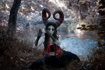 Fairytale photo with demonic horned faun playing on the jawbone of an animal