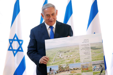 Israeli Prime Minister Benjamin Netanyahu holds up a placard given to him as a gift from Israeli residents of the area, at the start of a weekly cabinet meeting in the Jordan Valley, in the Israeli-occupied West Bank