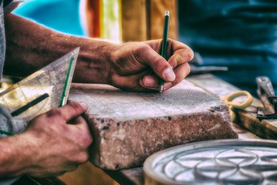 Hand von Steinmetz beim skizzieren