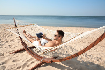 Young man with tablet in hammock on beach