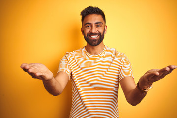 Young indian man wearing t-shirt standing over isolated yellow background smiling cheerful offering hands giving assistance and acceptance.