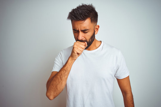 Young indian man wearing t-shirt standing over isolated white background feeling unwell and coughing as symptom for cold or bronchitis. Healthcare concept.