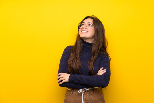 Teenager girl over isolated yellow wall looking up while smiling