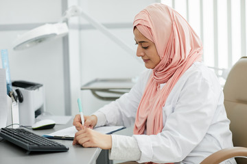 Portrait of young Middle-Eastern woman wearing hijab working as nurse in medical clinic and filling patients form at desk, copy space