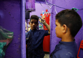 An Iraqi boy Ibrahim Qaesar Mohammed, 11 years old, who works at an generators-repair shop, looks at a mirror as he combs his hair at his home in Baghdad
