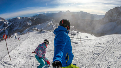 A skiing man and snowboarding woman going down the slope in Nassfeld, Austria. Man is holding a selfie still and taking the picture. Both wear sport helmets. Mountain ranges covered with snow. Freedom