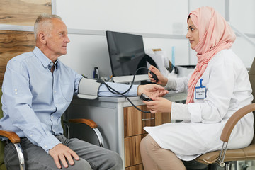 Side view portrait of young Arab woman working as doctor in medical clinic and measuring blood pressure of senior patient, copy space