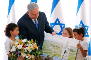 Israeli Prime Minister Benjamin Netanyahu looks at a placard, part of a gift presented to him from Israeli residents of the area, at the start of a weekly cabinet meeting in the Jordan Valley, in the Israeli-occupied West Bank