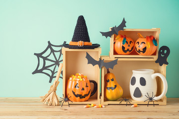 Halloween holiday concept with jack o lantern cup, candy corn and decorations on wooden table