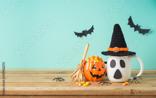 Halloween holiday concept with jack o lantern cup, candy corn, witch hat and decorations on wooden table