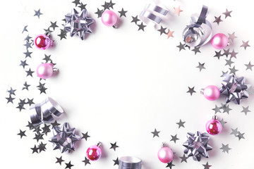 Christmas border of silver and pink pastel decoration, balls , tinsel, star, glitter on white. Xmas background. Flat lay style. Top view with copy space