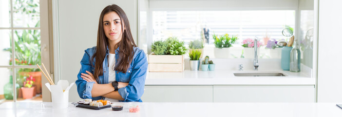 Wide angle picture of beautiful young woman eating delivery sushi skeptic and nervous, disapproving expression on face with crossed arms. Negative person.