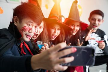 Young Asian people, a group of five persons, in scary costumes selfie their own photo. Group of friends having fun at a party in a nightclub to celebrate Halloween festival.