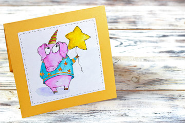 Watercolor Greeting Card with little funny pig and asterisk on white wooden background