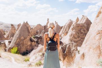 A blonde girl runs across the mountains in Turkey in Cappadocia. Follow me.