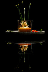 Prawn ballotine on lobster bisque. Exquisite dish. Creative restaurant meal concept. Haute couture food on black with reflection. Fine dining concept.