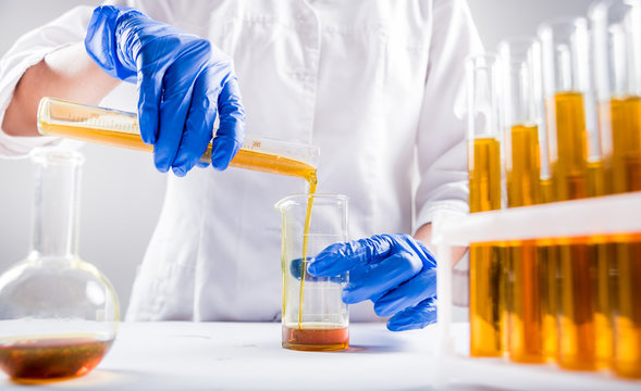 Scientist pouring organic oil. Beauty and cosmetics sciences. Laboratory equipment