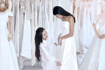 Cute Tailor check wedding dress size for beautiful Asian bride during dress fitting in tailoring room