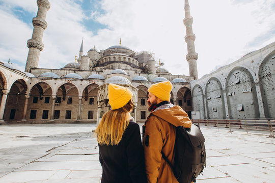 A young European couple walks in the courtyard of the Blue Mosque in Istanbul, Turkey. Traveler guy and girl in yellow hats walk in winter Istanbul. cloudy autumn day in Istanbul.