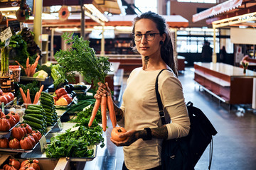 Beautiful pensive girl in glasses is buying fresh carrots at local farmer's market.