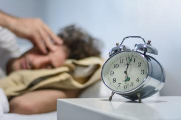Young latin man sleeping with alarm clock. Fototapete