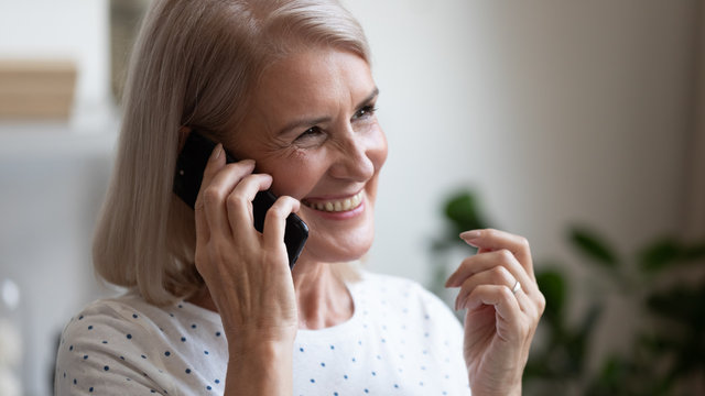 Happy beautiful mature woman making phone call close up