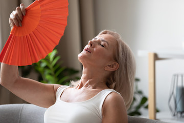 Exhausted older woman waving fan close up, suffering from heat