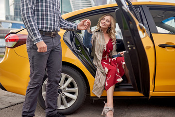 Photo of man giving hand to happy blonde in long dress sitting in taxi
