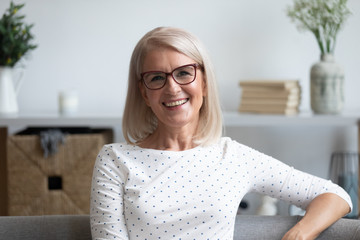 Head shot portrait smiling mature woman in glasses at home