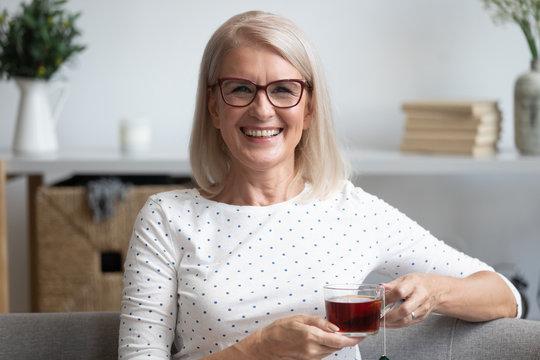 Head shot portrait smiling mature woman holding cup of tea