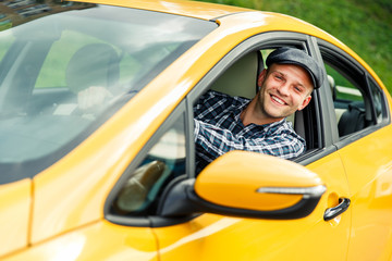 Image of happy driver in plaid shirt sitting in yellow taxi on summer