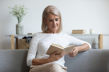 Beautiful mature woman reading book, sitting on couch at home