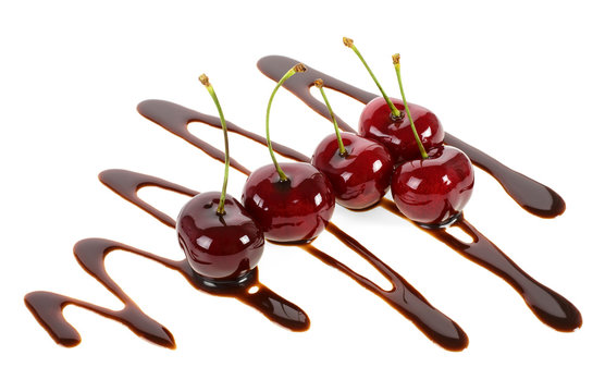 Group of ripe cherries dipped in melted chocolate on a white background